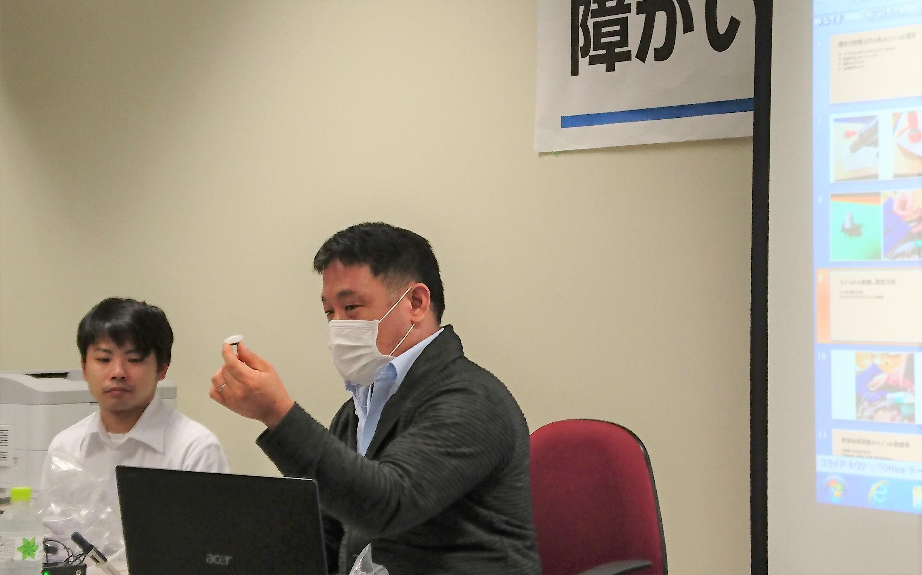 ハート義肢の吉原さんと島袋さんが座ってスイッチの説明をしている